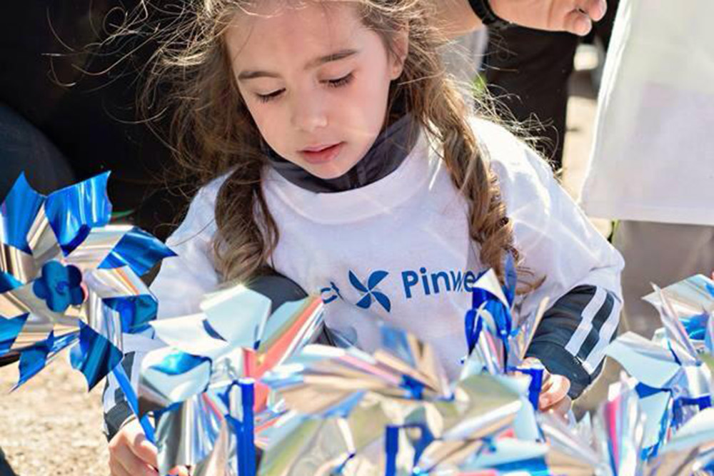 a girl playing with pinwheels in the community